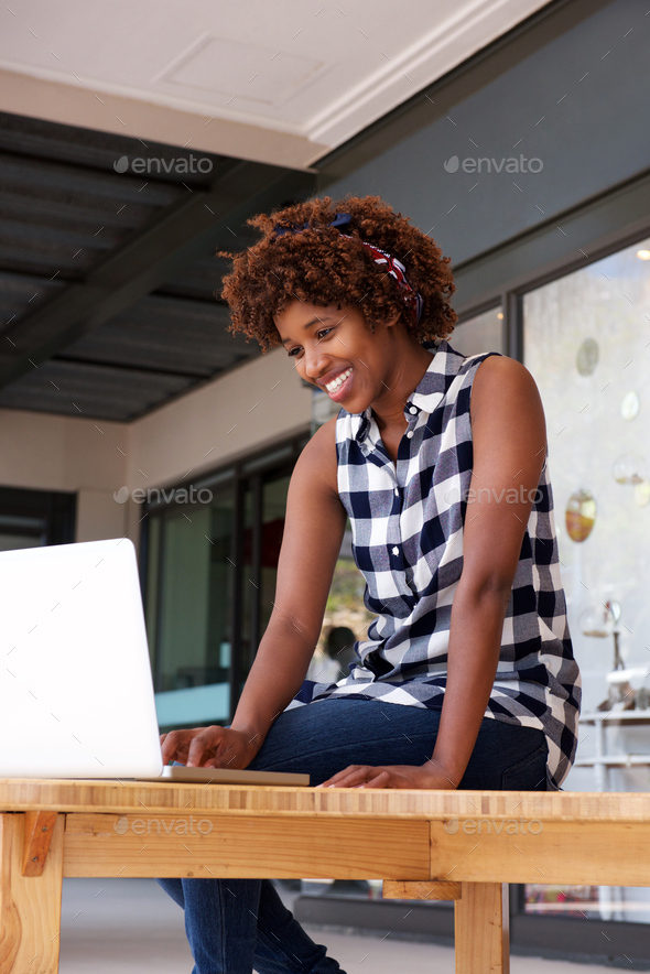smiling african woman using laptop - Stock Photo - Images