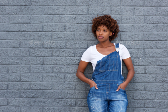 african woman in dungarees by gray wall - Stock Photo - Images