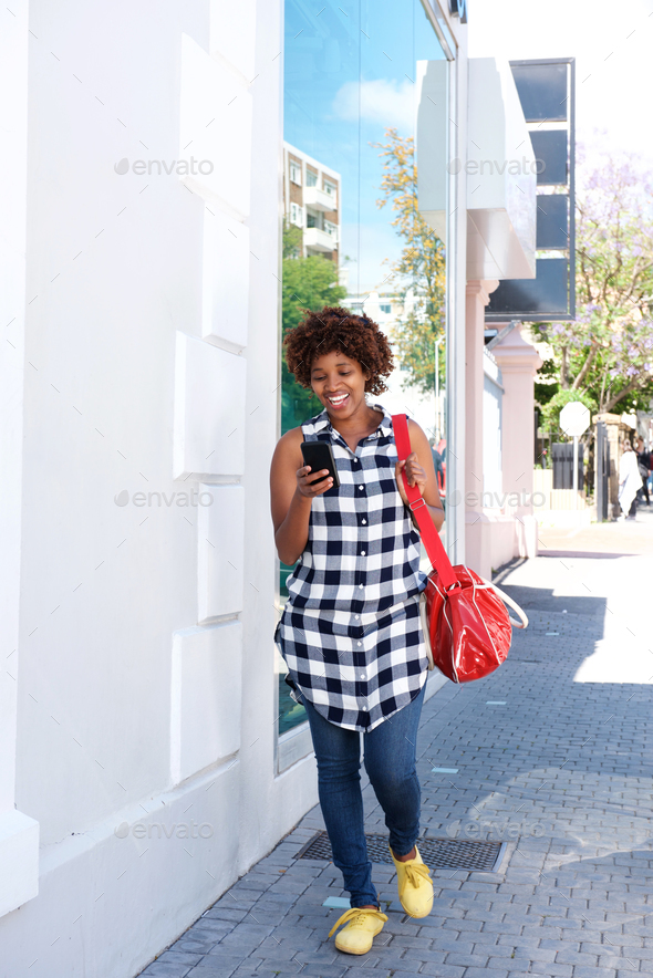 african woman walking with cellphone and bag in the city - Stock Photo - Images