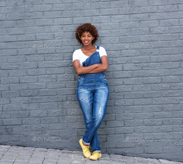 smiling african woman standing against gray wall - Stock Photo - Images