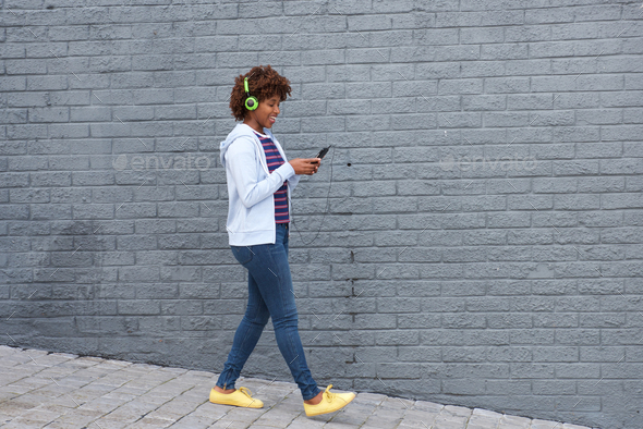 african woman walking and listening to music on mobile phone - Stock Photo - Images