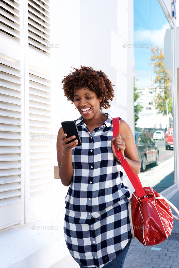 happy african woman walking in the city with cellphone and bag - Stock Photo - Images