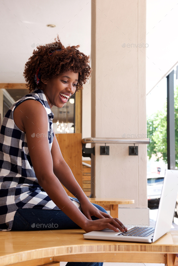 african woman smiling with laptop computer - Stock Photo - Images