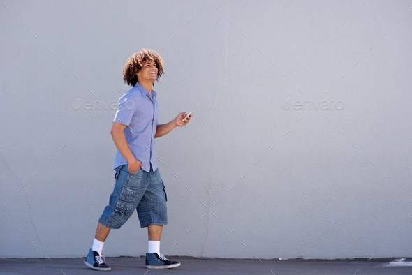 young afro man walking with cellphone - Stock Photo - Images