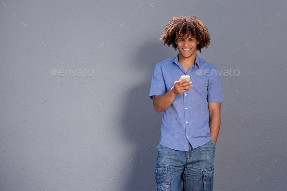 smiling afro man holding cellphone - Stock Photo - Images