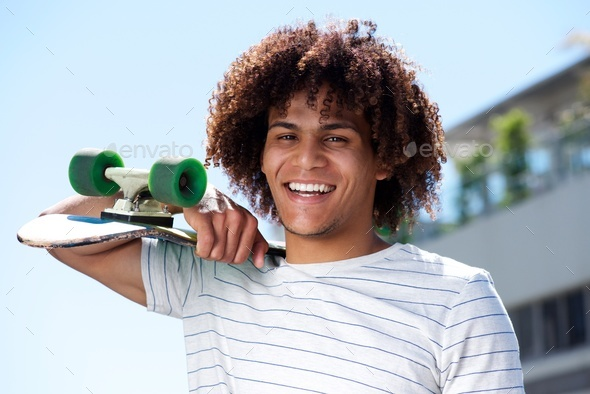 happy young guy smiling outside with skateboard - Stock Photo - Images