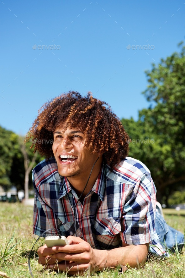 happy young man laughing with cellphone and earphones in park - Stock Photo - Images