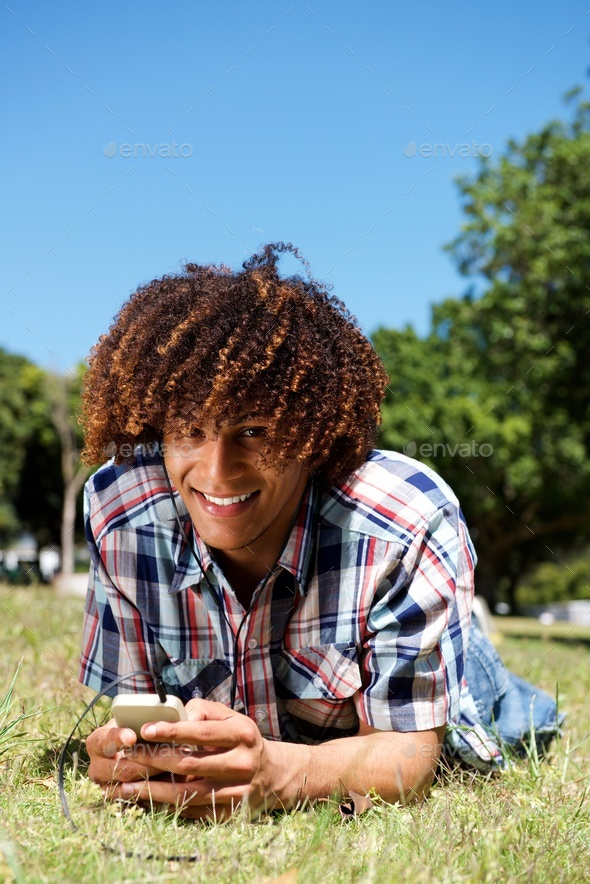 smiling young afro man lying down on grass in park holding phone - Stock Photo - Images