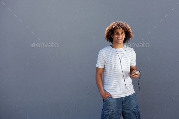 happy young man smiling with smart phone and earphones - Stock Photo - Images