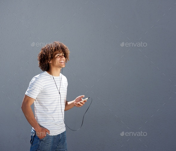 man walking outside and listening to music with smart phone - Stock Photo - Images