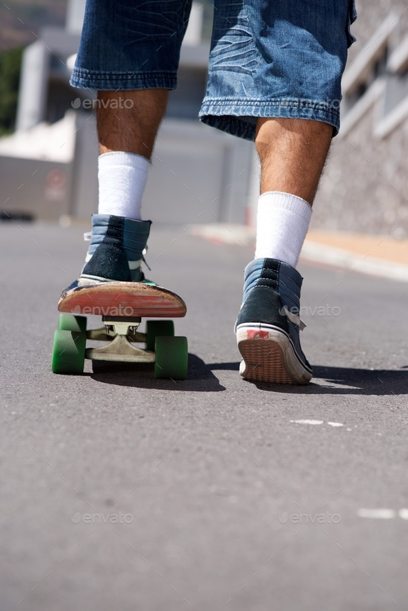 back of man skateboarding on street - Stock Photo - Images