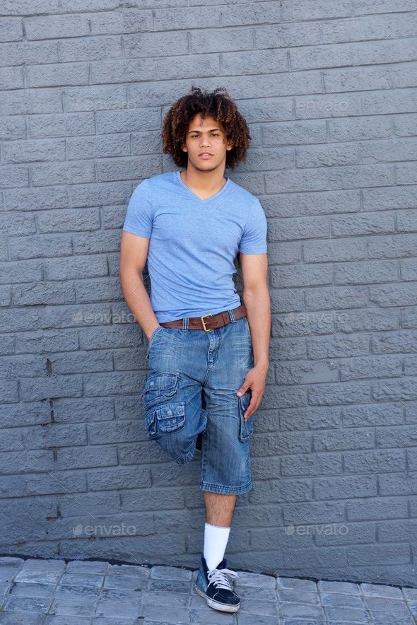 Full length cool young guy leaning against grey wall - Stock Photo - Images