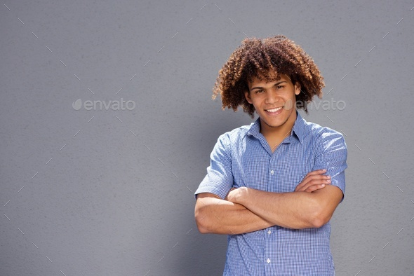 smiling handsome young man against gray background - Stock Photo - Images