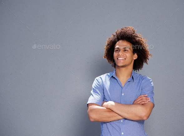smiling confident man standing with arms crossed - Stock Photo - Images