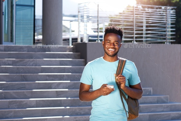 smiling african student walking by stairs with bag and smart phone - Stock Photo - Images