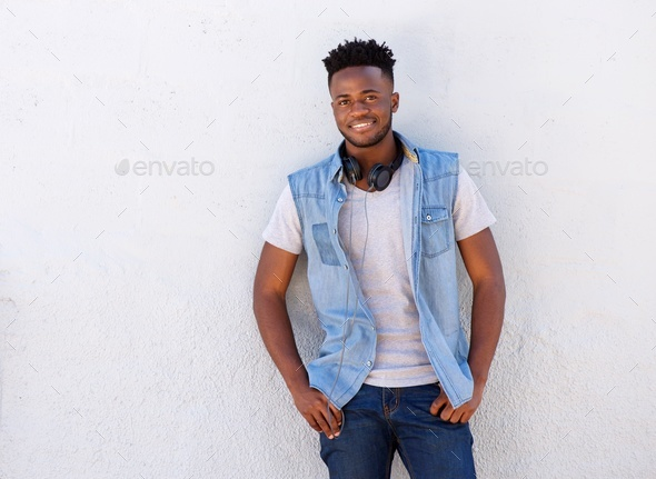 smiling man with headphones standing against white wall - Stock Photo - Images