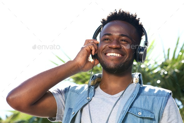 Close up happy young black man listening to music with headphones - Stock Photo - Images