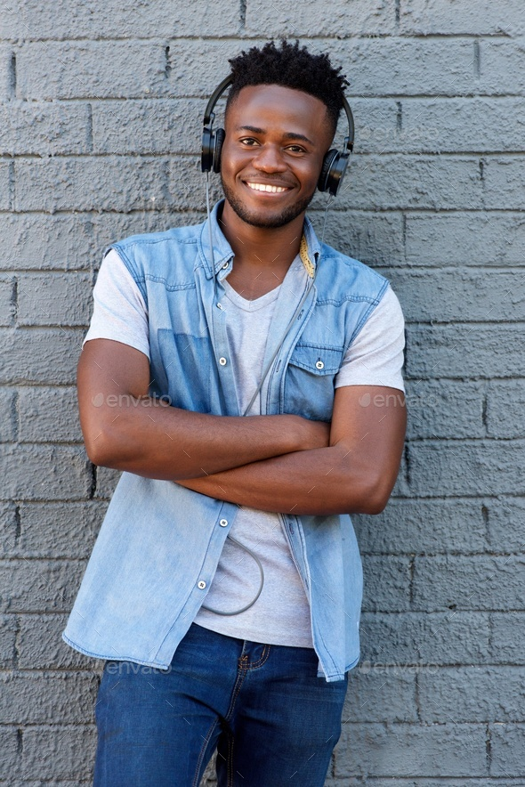 smiling man with headphones standing with arms crossed - Stock Photo - Images