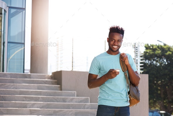 smiling african student holding cellphone and bag on campus - Stock Photo - Images