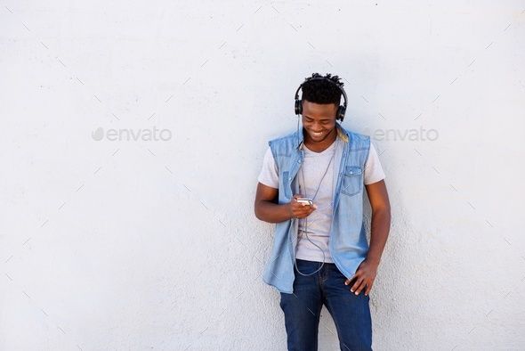 smiling black man leaning against wall with smart phone and headphones - Stock Photo - Images