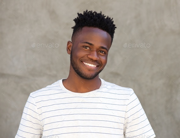 happy african man with beard smiling by wall - Stock Photo - Images