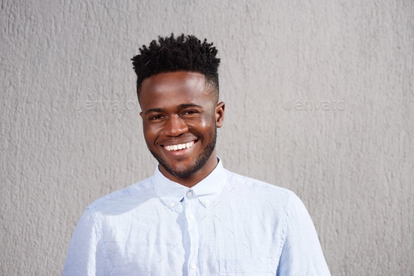 attractive African man smiling and standing by wall - Stock Photo - Images