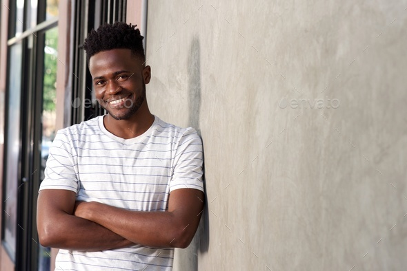 attractive young african man leaning on wall with arms crossed - Stock Photo - Images