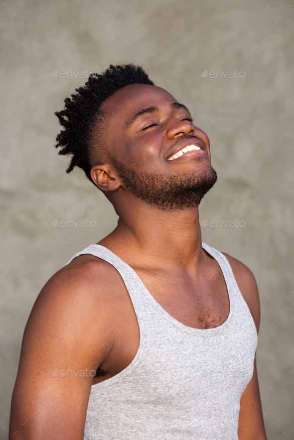 handsome young man smiling with eyes closed - Stock Photo - Images