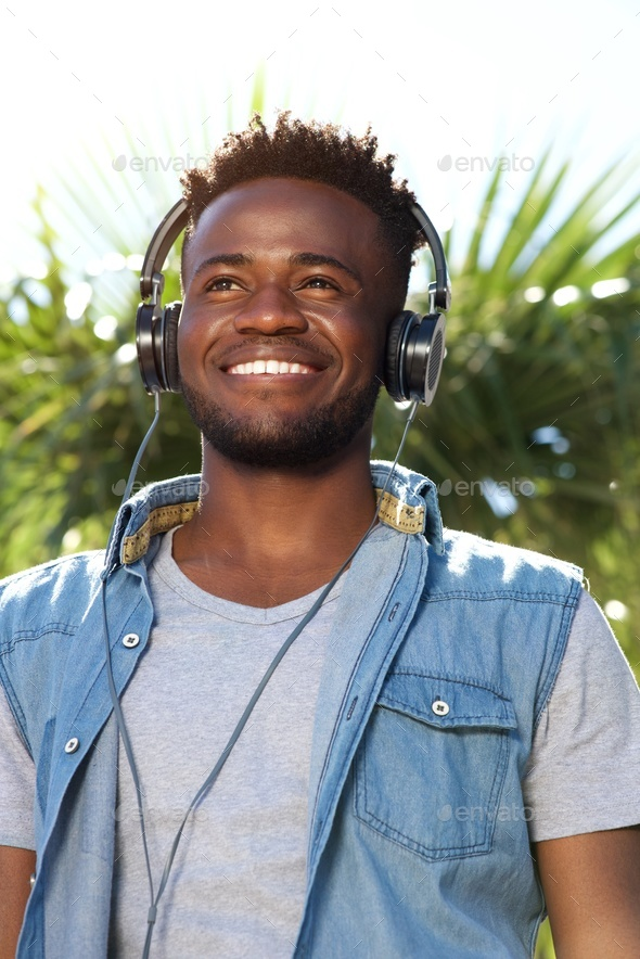 young black man smiling with headphones outside - Stock Photo - Images