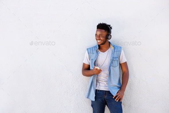 smiling man with headphones and cellphone standing by white wall - Stock Photo - Images