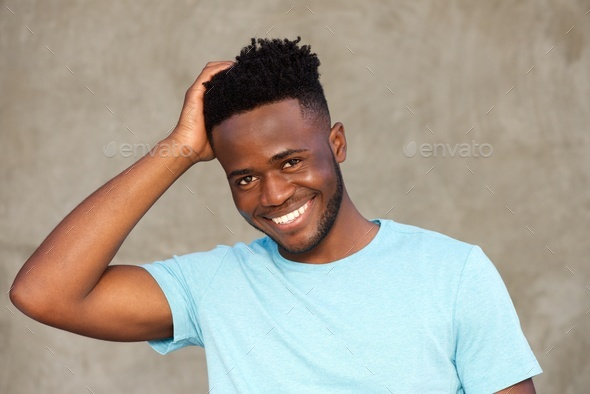 handsome african man smiling and standing with hand in hair - Stock Photo - Images