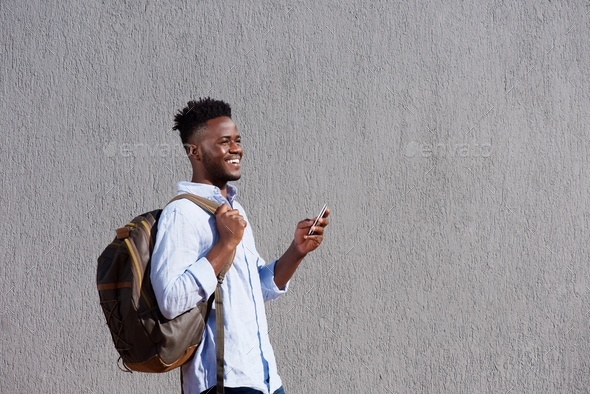 handsome black man with bag and cellphone walking by wall - Stock Photo - Images