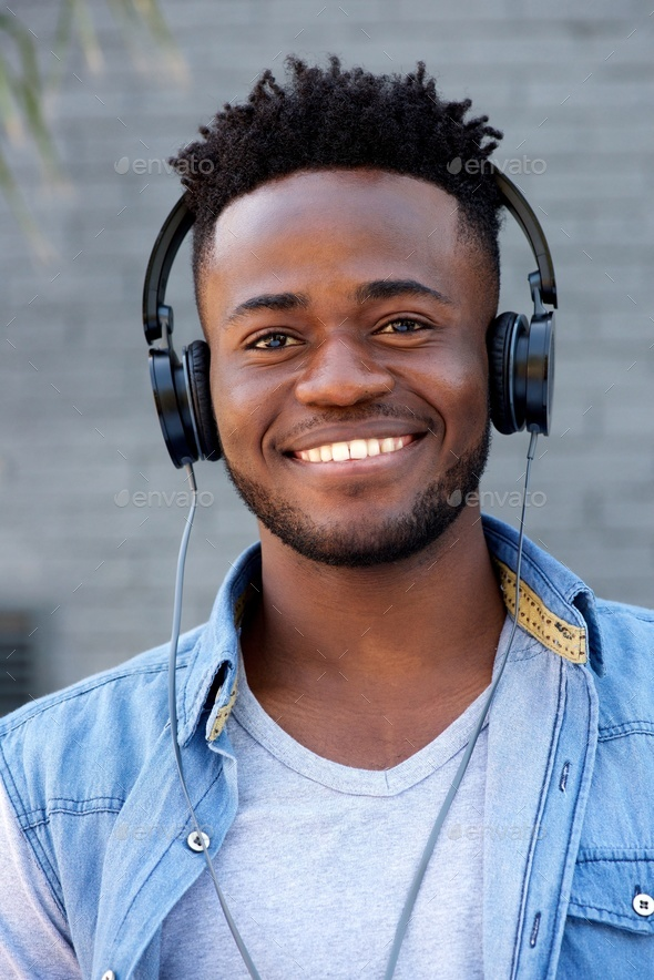 Close up cool young black guy listening to music with headphones - Stock Photo - Images