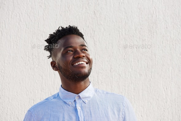 attractive man laughing and standing by wall - Stock Photo - Images