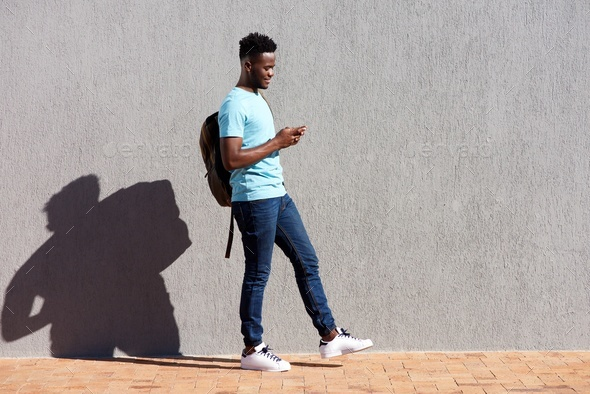 College student walking with bag and mobile phone - Stock Photo - Images