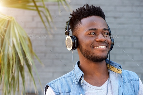 young african man smiling with headphones by palm tree - Stock Photo - Images