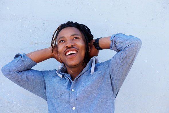 cheerful african man laughing with hands behind head - Stock Photo - Images