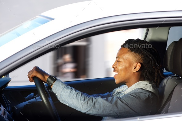 happy young black man driving car - Stock Photo - Images