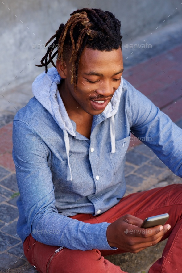 happy african man sitting outside on sidewalk with cellphone - Stock Photo - Images
