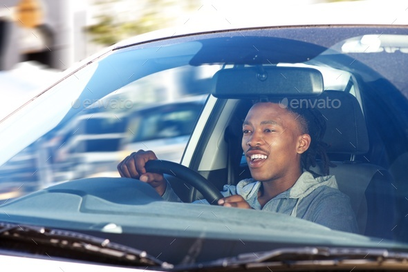 smiling african man driving car in city - Stock Photo - Images