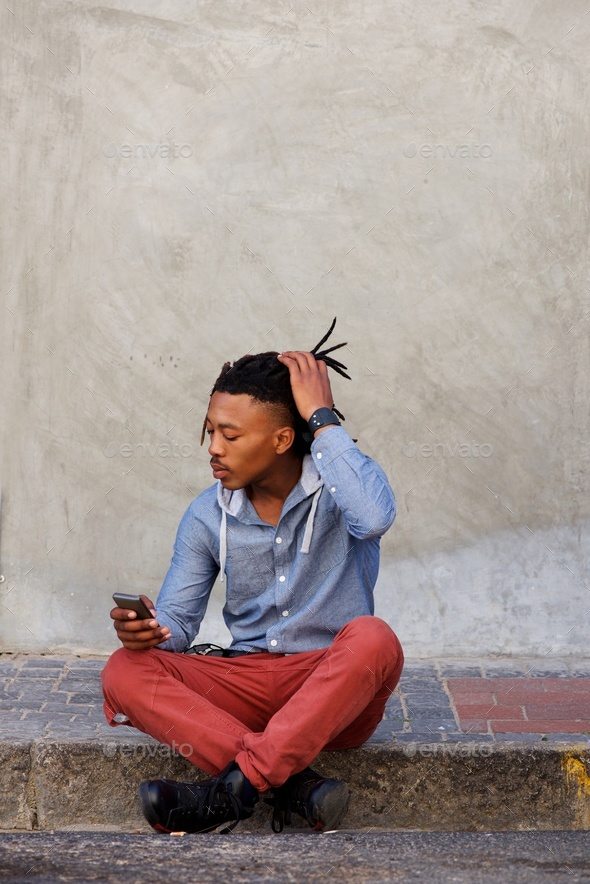 modern african man sitting outside with mobile phone - Stock Photo - Images