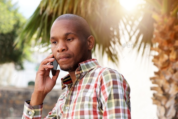 handsome young african man talking on mobile phone outside - Stock Photo - Images