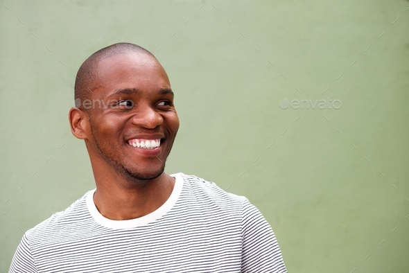 confident young black man looking sideways and smiling - Stock Photo - Images