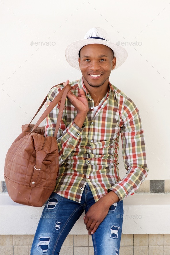 young african travel man sitting outdoors with bag - Stock Photo - Images