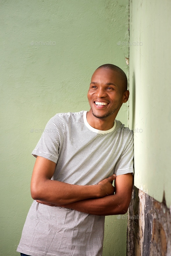 young afro american man leaning to wall and smiling - Stock Photo - Images