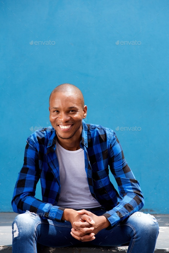 stylish young man sitting outside and smiling - Stock Photo - Images