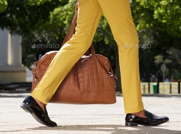 side view of man walking outdoors on city street with bag - Stock Photo - Images