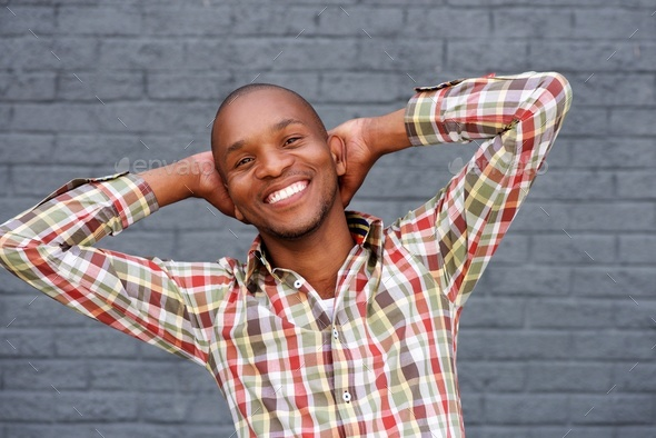 young man smiling with hands behind head against gray wall - Stock Photo - Images