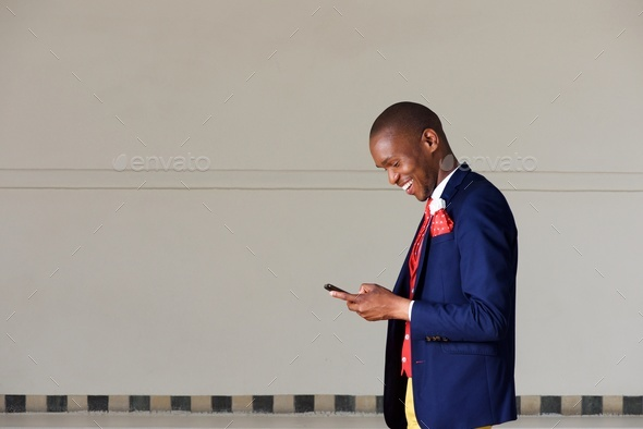 young businessman using mobile phone and walking outdoors - Stock Photo - Images