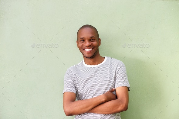 smiling young african man standing against green wall - Stock Photo - Images
